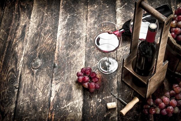 Weinhintergrund rotwein mit gläsern mit trauben auf einem hölzernen hintergrund