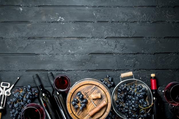 Weinhintergrund. rotwein mit trauben und einem alten fass. auf einem schwarzen rustikalen tisch.