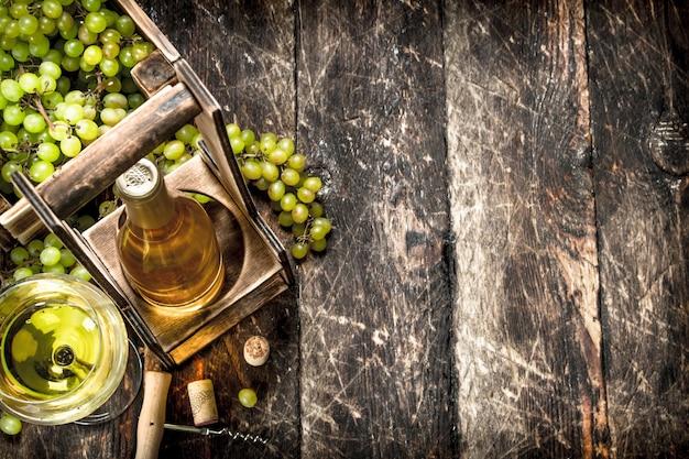 Weinhintergrund weißwein auf einem stand mit zweigen der frischen trauben auf einem hölzernen hintergrund