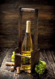 Weinhintergrund. weißwein auf einem stand mit zweigen frischer trauben. auf einem hölzernen hintergrund.