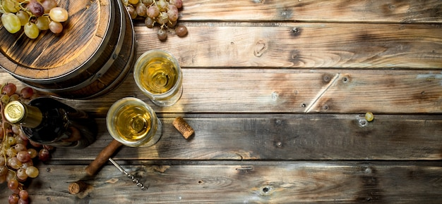 Weinhintergrund. weißwein in einem alten fass. auf einem hölzernen hintergrund