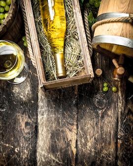 Weinhintergrund. weißwein mit einem eimer grüner trauben. auf einem hölzernen hintergrund.