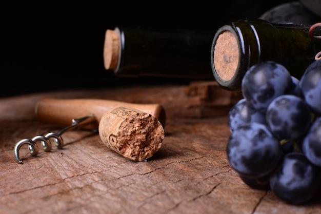 Weinkeller mit trauben, korkenzieher und flaschen