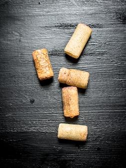 Weinkorken. auf einem schwarzen hölzernen hintergrund.