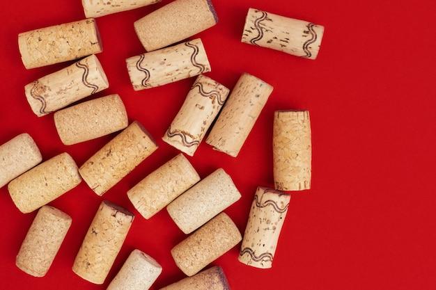 Weinkorken auf rotem papierhintergrund mit kopienraum. close up gebrauchte holzstopfen. konzept für rotwein.