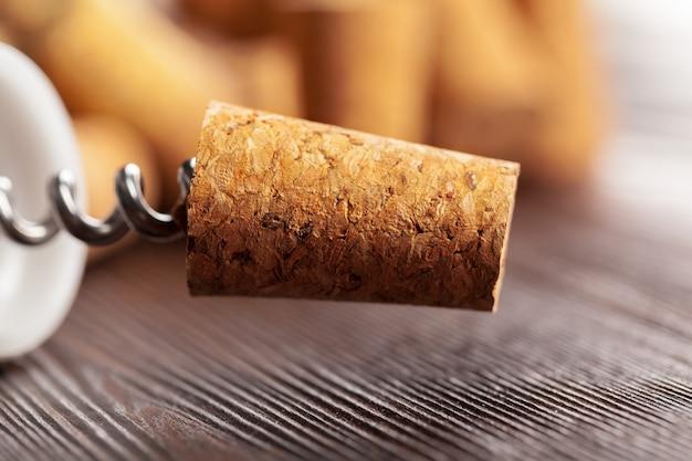 Weinkorken mit korkenzieher auf holztisch