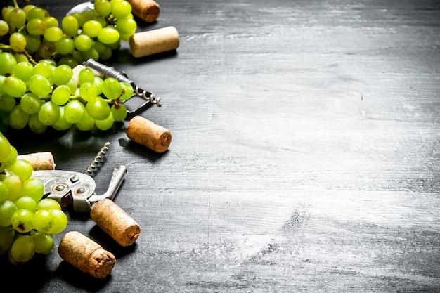 Weinkorken mit korkenzieher und traubenzweig. auf einem schwarzen hölzernen hintergrund.