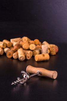 Weinkorken und korkenzieher auf schwarzem tisch