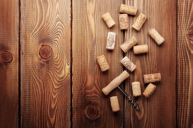 Weinkorken und korkenzieher über rustikalem holztischhintergrund. ansicht von oben mit kopienraum