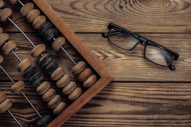 Weinlese-abakus mit gläsern auf einem holz. Premium Fotos