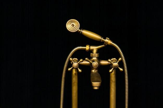 Weinlese alter messingwasserhahn mit duschkopf lokalisiert auf schwarzer oberfläche
