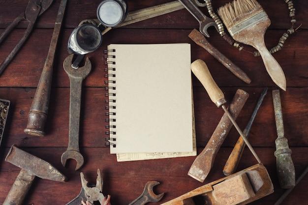 Weinlese-arbeitswerkzeug, notizbuch auf dunklem hölzernem hintergrund.