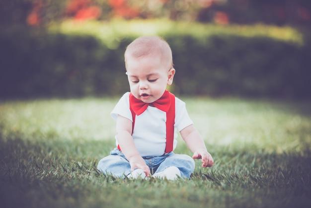 Weinlese-baby mit rotem hosenträger in im freien