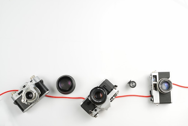 Weinlese der fotografischen ausrüstung, arbeitsplatzkonzept mit grünem blatt auf weißem hintergrund.