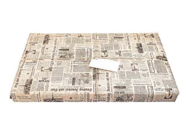 Weinlese-geschenkbox-paket mit leerem geschenkanhänger auf altem hölzernem hintergrund.