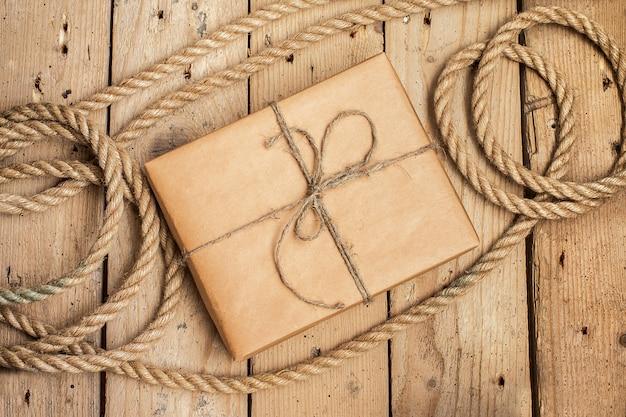 Weinlese-geschenkbox und seil auf hölzernem hintergrund