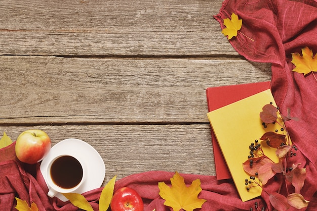 Weinlese-herbsttabelle mit äpfeln, gefallenen blättern, tasse kaffee oder tee auf altem holztischhintergrund