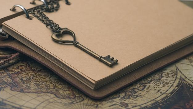 Weinlese-herz-geformter schlüssel auf tagebuchbuch