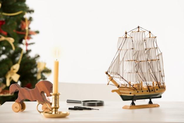 Weinlese-hölzernes pferd und schiff auf sankt arbeitstabelle, weihnachtsbaum auf hintergrund
