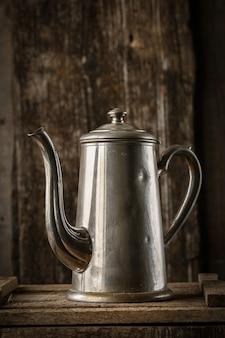 Weinlese-kaffeekanne auf rustikalem hölzernem hintergrund