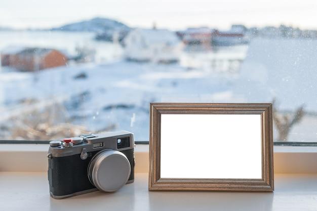 Weinlese-kamera mit leerem bilderrahmen auf fensterbrett