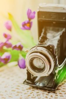 Weinlese-kamera mit schönem blumenstrauß von blumen auf gestrickter tischdecke. altes weinlesestillleben konzept.