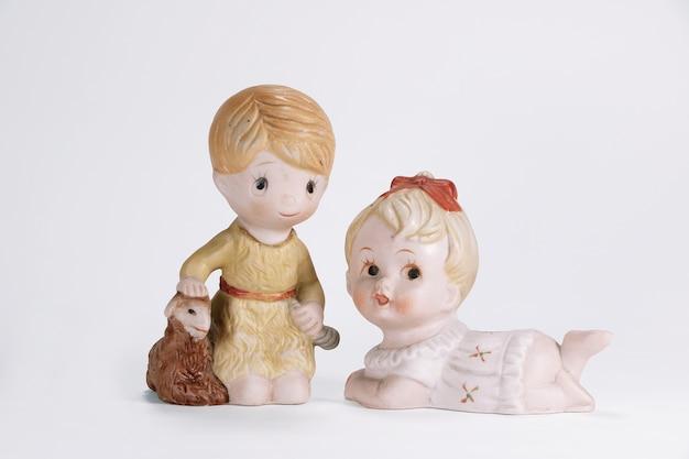 Weinlese-keramikpuppe des jungen und des babymädchens für den weißen hintergrund der innendekoration.