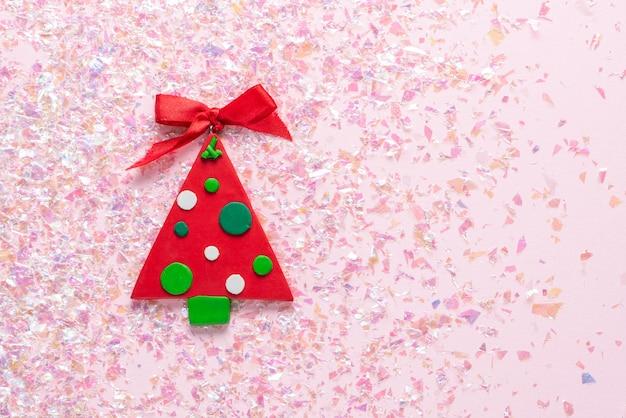 Weinlese-plasticinelehm weihnachtsbaum auf rosa funkeln. minimal weihnachten. frohes neues jahr. flache lage, draufsicht, copyspace
