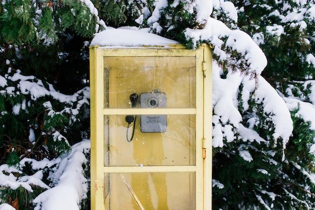 Weinlese-retro-anrufbox im winterstadtpark, schneelandschaft
