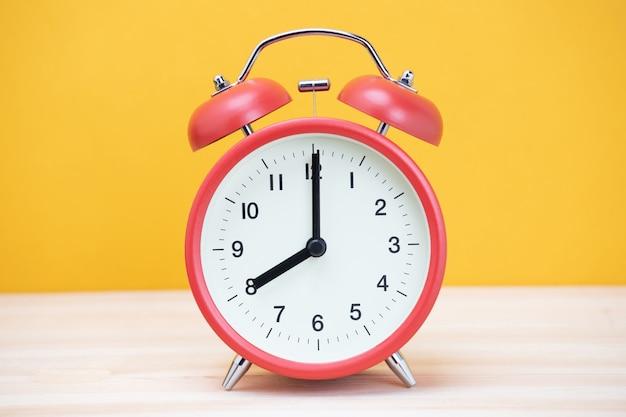 Weinlese retro wecker acht minuten bis zwölf uhr auf tischholz mit gelber wand.