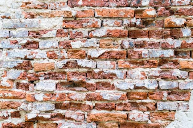 Weinlese rissiger roter backstein und betonwand
