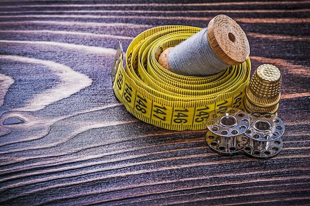 Weinlese-rolle der fadenmessband-fingerhutspulen auf holzbrett-handwerkskonzept