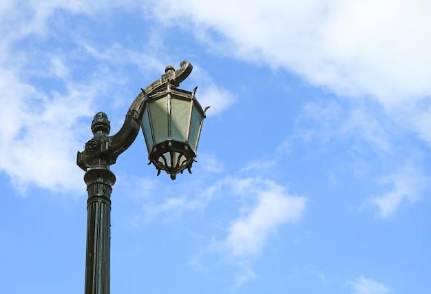Weinlese-schwarzer laternenpfahl gegen bewölkten blauen himmel
