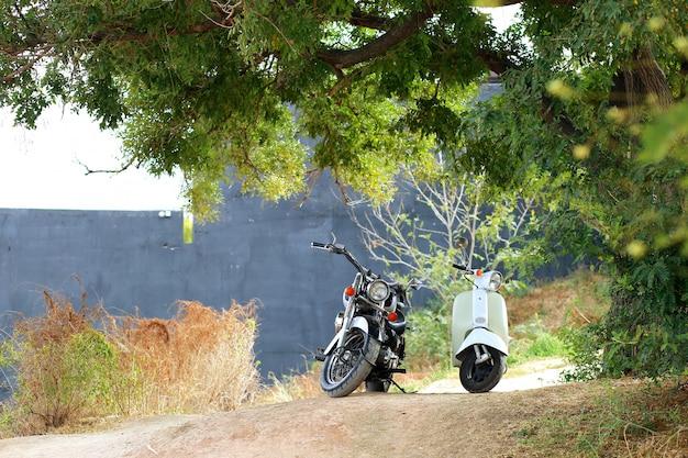 Weinlese schwarzes motorrad, das nahe weißem motorrad in den sonnenstrahlen steht. seitenansicht