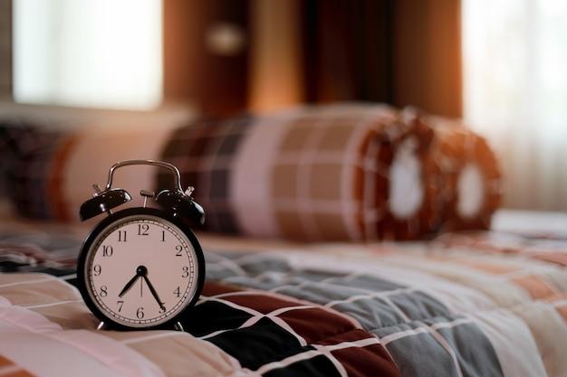 Weinlese-wecker auf schlafzimmer morgens mit sonnenaufgang an den fenstern. schlafen im winter oder herbst
