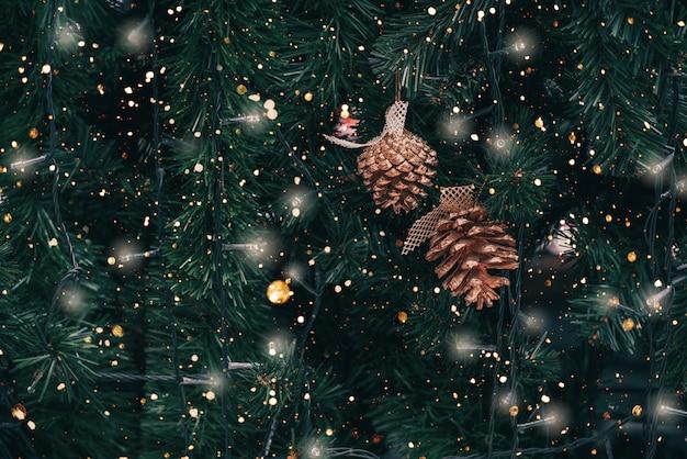 Weinlese-weihnachtsbaum mit kiefernkegeldekoration und scheinlicht.