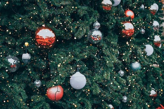 Weinlese-weihnachtsbaum mit roter ballverzierung und dekoration, scheinlicht. weihnachts- und neujahrsfeiertagshintergrund. vintage farbton.