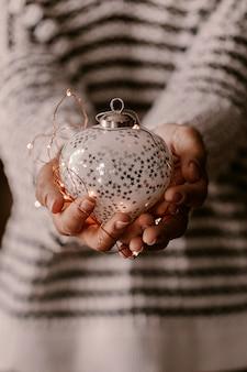 Weinlese-weihnachtsbaumschmuck in den frauenhänden