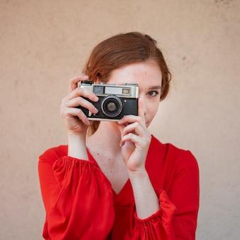 Weinleseartportrait einer frau, die eine kamera anhält