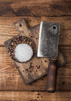 Weinlesebeil für fleisch auf hölzernem schneidebrett mit salz und pfeffer auf hölzernem hintergrund.