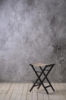 Weinlesedachbodeninnenraum mit bretterboden, strukturierter gealterter grauer beton an der wand und stuhl