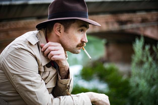 Weinlesedetektiv, der eine sigarette raucht und niedergedrückt schaut