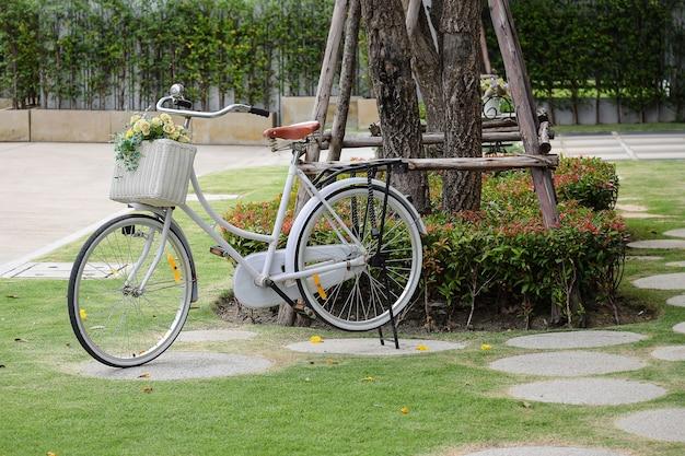 Weinlesefahrrad am garten mit künstlichen blumen im korb