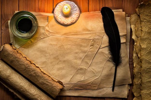 Weinlesefeder mit papier und tinte auf tisch im licht der kerze