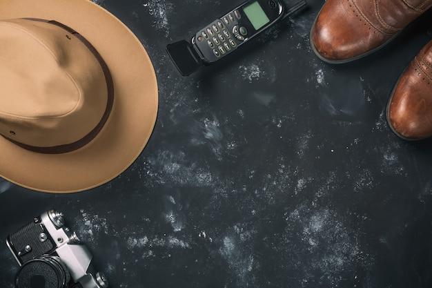 Weinlesefilmkamera, braune schuhe, fedorahut und alter handy auf schwarzem stein