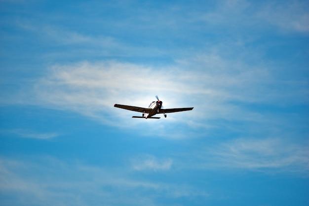 Weinleseflugzeug steigt im himmel am hellen tag an.