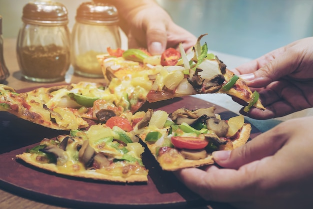 Weinlesefoto der pizza mit dem bunten gemüsebelag bereit gegessen zu werden