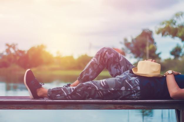 Weinlesefoto des entspannenden mannes mit dem genießen von frischluft auf hölzernem balkon durch fluss.