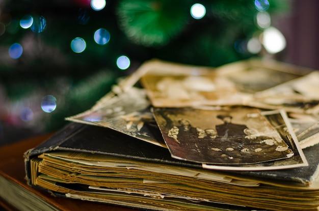 Weinlesefotoalbum mit familienfotos auf weihnachtsbaumhintergrund
