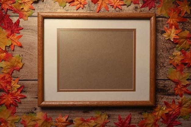 Weinlesefotorahmen mit herbstahornblättern auf hölzernem hintergrund.